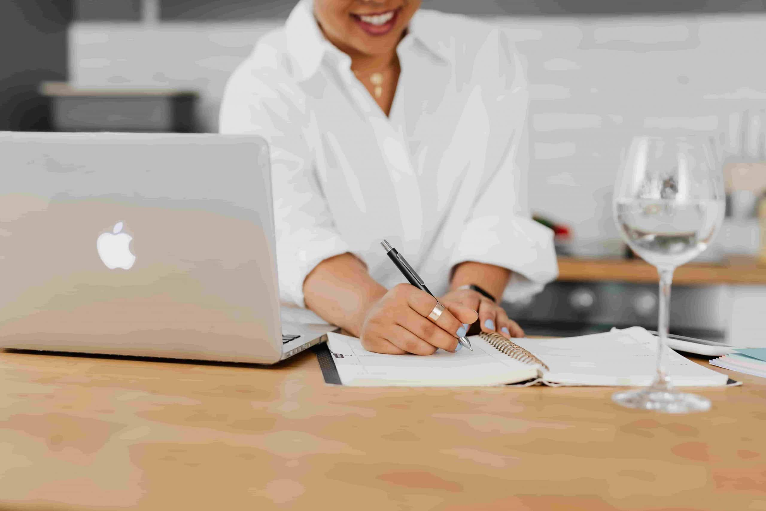 Webinar Transcription for SEO; woman taking notes in her notepad and working on her Macbook; a wine glass placed on the table