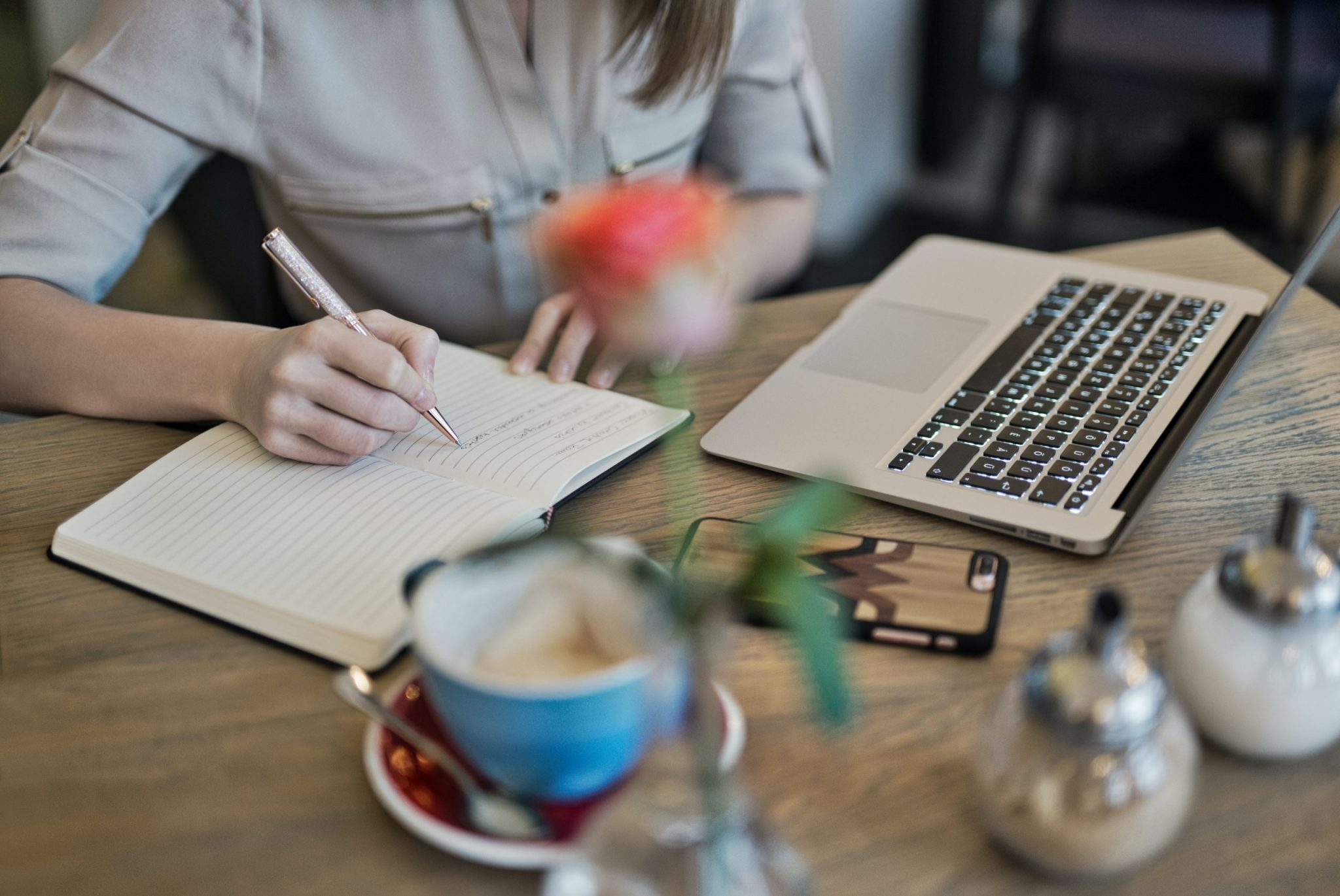 A woman taking notes while working on her laptop
