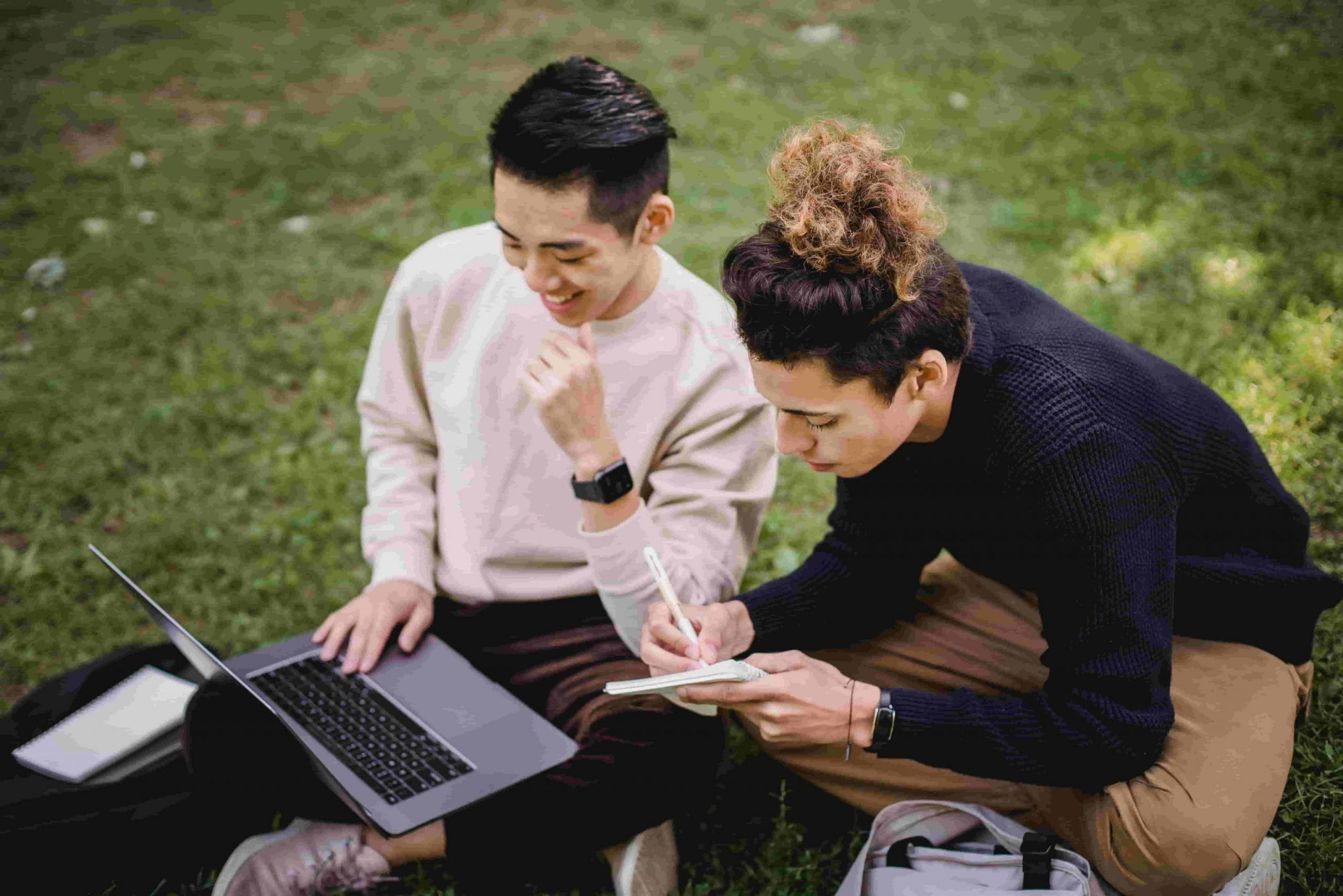 Webinar Transcription for SEO; two men sitting in a park and discussing work on their laptop while taking notes